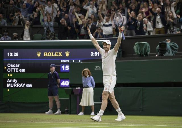 Andy Murray raises his arms to the Centre Court crowd after battling past Oscar Otte