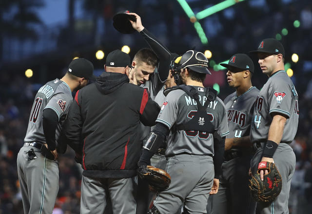 Arizona Diamondbacks pitcher Patrick Corbin, center left, removes his cap as he wipes his face during a mound visit in the seventh inning of a baseball game against the San Francisco Giants on Tuesday, June 5, 2018, in San Francisco. (AP Photo/Ben Margot)