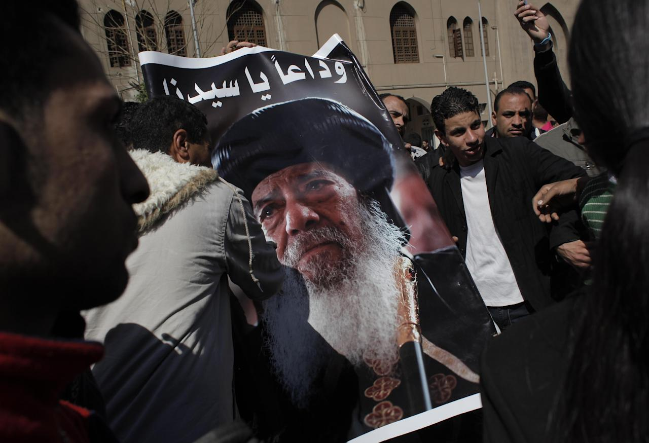 "Egyptian Coptic mourners carry a picture of the late Pope Shenouda III while gathering outside the Coptic Orthodox Church for the viewing of the body of Pope Shenouda III in Cairo, Egypt, Sunday, March 18, 2012. Pope Shenouda III, the patriarch of the Coptic Orthodox Church who led Egypt's Christian minority for 40 years during a time of increasing tensions with Muslims, died Saturday. He was 88. The Arabic writing reads, ""goodbye, our master."" (AP Photo/Nasser Nasser)"