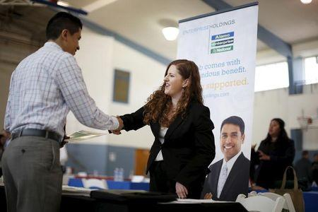 Jessica Kolber shakes hands with a job seeker at a job fair in Burbank, Los Angeles