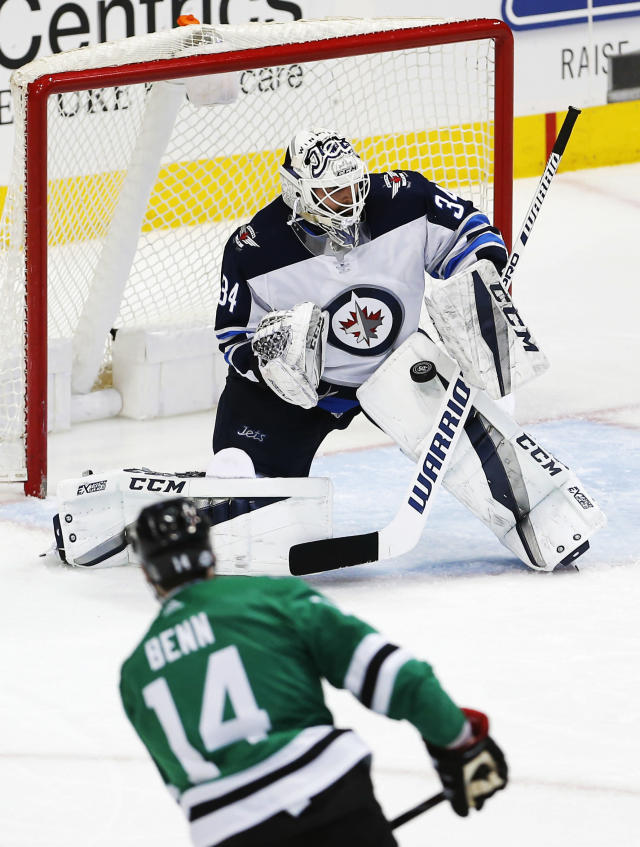 Winnipeg Jets goaltender Michael Hutchinson (34) stops a shot from Dallas Stars forward Jamie Benn (14) during the third period of an NHL hockey game, Saturday, Feb. 24, 2018, in Dallas. (AP Photo/Brandon Wade)