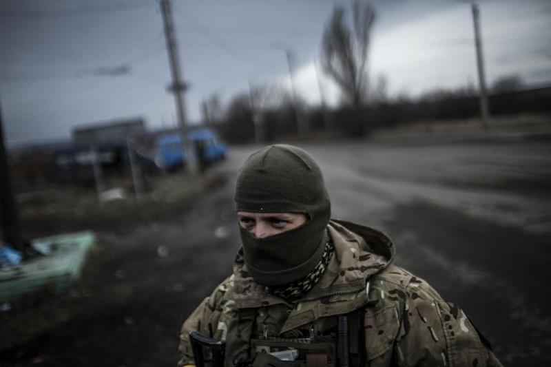 A Ukrainian soldier stands watch on a road between Debaltseve and the Ukrainian-controlled town of Artemivsk, in the Donetsk region, on February 2, 2015 (AFP Photo/Manu Brabo)