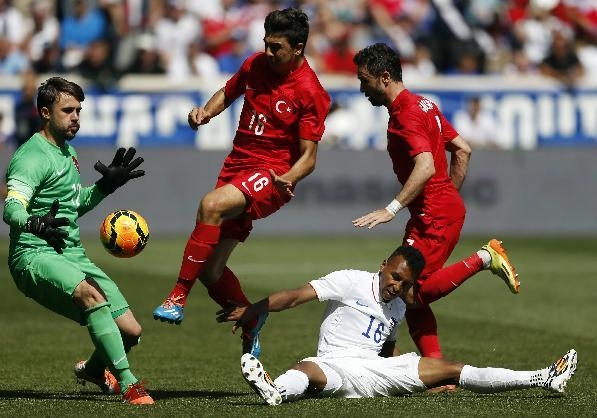 United States' Julian Green (16) goes down while trying to score on Turkey goalkeeper Onur Recep Kivrak, left, in the second half of an international soccer friendly, Sunday, June 1, 2014, in Harrison, N.J. Also defending are Ozan Tufan, center, and Gokhan Gonul. The U.S. won 2-1. (AP Photo/Julio Cortez)