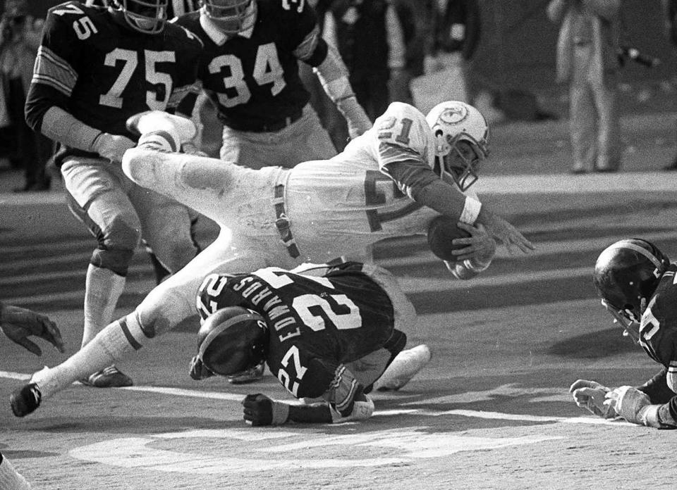 """FILE - In this Dec. 31, 1972, file photo, Miami Dolphins Jim Kiick goes headfirst over Pittsburgh Steelers"""" Glen Edwards as Kiick scores in third quarter of the AFC championship game at Pittsburgh's Three Rivers Stadium. Former running back Kiick, who helped the Dolphins achieve the NFLs only perfect season in 1972, has died at age 73. In recent years Kiick battled memory issues and lived in an assisted living home, and the team announced his death Saturday, June 20, 2020. (AP Photo, File)"""
