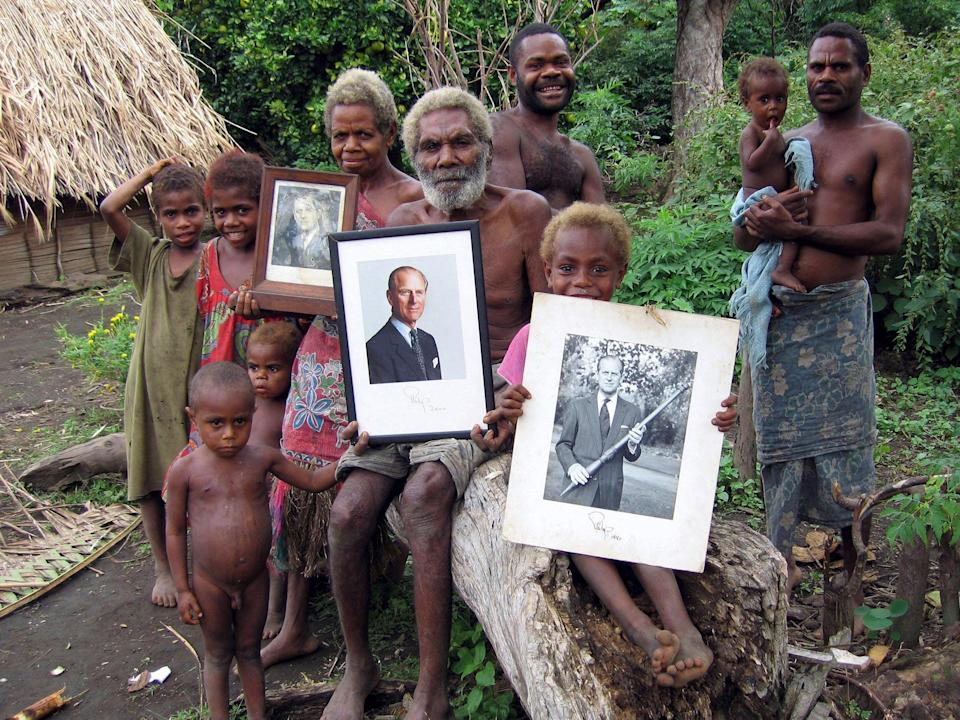Villagers on the island of Tanna hold up treasured photos of Prince Philip (Richard Shears/Shutterstock)
