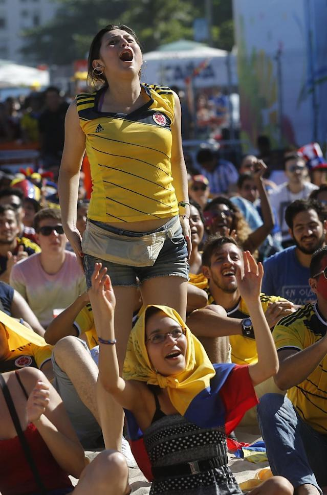 Colombia soccer fans cheer during their team's World Cup game against Greece inside the FIFA Fan Fest area on Copacabana beach in Rio de Janeiro, Brazil, Saturday, June 14, 2014. (AP Photo/Silvia Izquierdo)