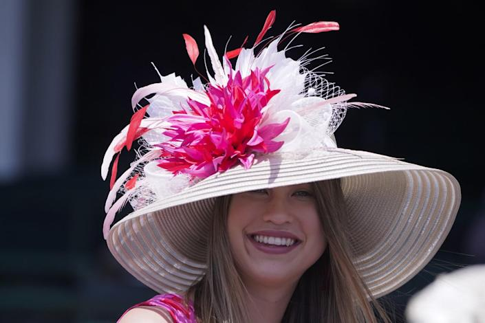 A woman smiles while wearing a white stripped brimmed hat with a pink and red flower and feathers on it.