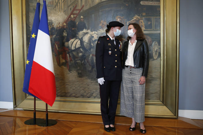 French math teacher-volunteer fighter, Marion Dehecq, left, poses with Paris-based Associated Press journalist Lori Hinnant, after she receives a bronze medal for courage and dedication as she used CPR to save the life of a jogger, during a ceremony with France's minister for citizenship issues, Marlene Schiappa at the Paris fire service headquarters in Paris, France, Monday, May 10, 2021. The jogger's wife, Paris-based Associated Press journalist Lori Hinnant, helped identify the anonymous rescuer by putting up thank-you signs in Monceau Park, where her husband Peter Sigal went into cardiac arrest on April 28. (AP Photo/Francois Mori, pool)