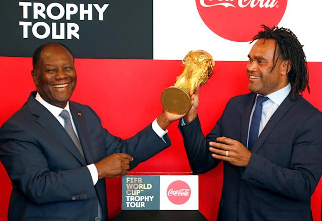 Ivorian president Alassane Ouattara Alassane Ouattara and French former soccer player Christian Karembeu hold the World Cup Trophy during the FIFA world cup tour ceremony at the presidential palace in Abidjan, Ivory Coast March 13, 2018. REUTERS/Luc Gnago