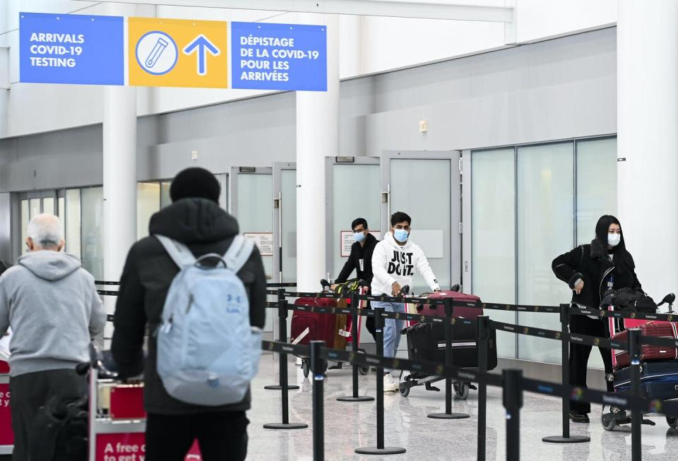"""<span class=""""caption"""">Arriving travellers from an international flight follow signs toward COVID-19 testing at Pearson International Airport in Toronto in February.</span> <span class=""""attribution""""><span class=""""source""""> THE CANADIAN PRESS/Nathan Denette </span></span>"""
