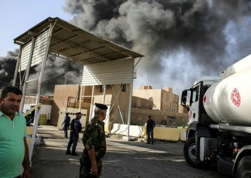Iraqi federal policemen stand outside the country's biggest ballot warehouse hit by a fire and where votes for the eastern Baghdad district were stored on June 10, 2018