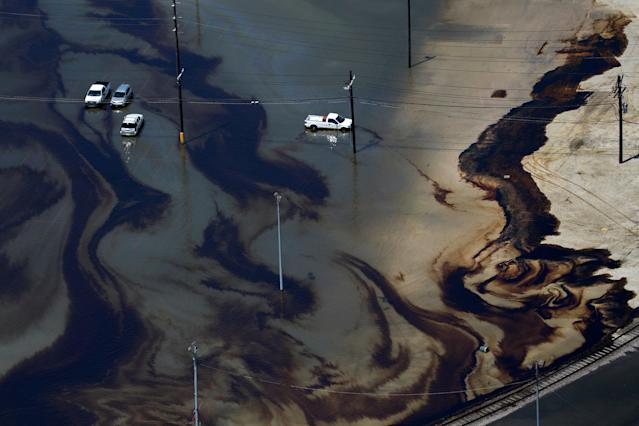 <p>Vehicles sit amid leaked fuel mixed in with flood waters caused by Tropical Storm Harvey in the parking lot of Motiva Enterprises LLC in Port Arthur, Texas, Aug. 31, 2017. (Photo: Adrees Latif/Reuters) </p>