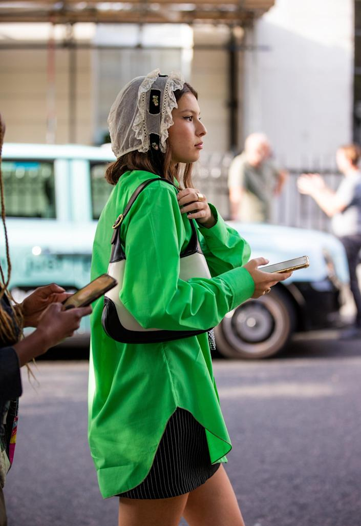 <p>An electric green button-down is an unexpected counter to a lace headpiece. </p>