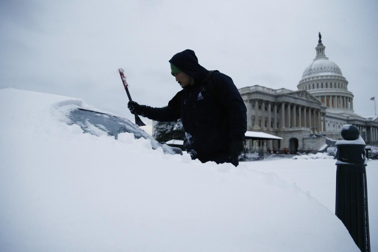 After finishing an overnight shift, a worker clears the snow from his car at the U.S. Capitol in Washington March 17, 2014. A winter storm landed a final punch on the U.S. mid-Atlantic states on Monday just days before spring begins, dumping more than a foot (30 cm) of snow in some places, shutting schools and federal offices and cancelling flights. The winter storm shut down federal offices in the nation's capital, and dozens of schools in the area also remained closed. REUTERS/Jonathan Ernst (UNITED STATES - Tags: POLITICS ENVIRONMENT)
