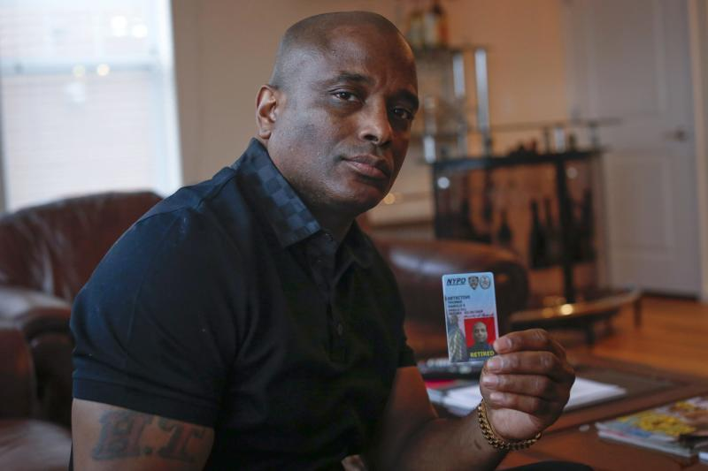 Retired NYPD detective Harold Thomas poses  with his retired NYPD identification card in West Hempstead, New York