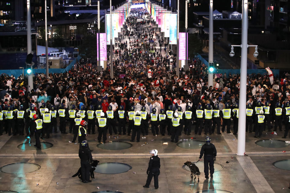 Soccer Football - Euro 2020 - Final - Fans gather for Italy v England - Wembley Stadium, London, Britain - July 11, 2021 Police officers stand guard as England fans gather during the match Action Images via Reuters/Peter Cziborra