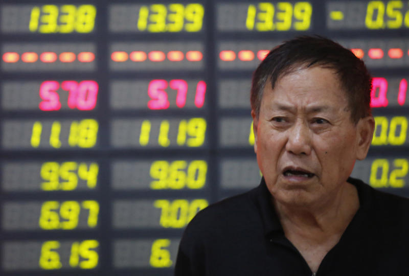 An investor stands in front of the stock price monitor at a private securities company in Shanghai, China Friday, July 26, 2013. Asian stock markets floundered Friday as China pressed ahead with industrial restructuring that is contributing to slowing growth in the world's No. 2 economy. (AP Photo)