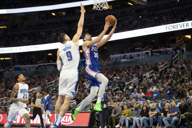 Philadelphia 76ers guard Furkan Korkmaz (30) attempts to lay up the ball against Orlando Magic center Nikola Vucevic (9) during the first half of an NBA basketball game in Orlando, Fla., Friday, Dec. 27, 2019. (AP Photo/Willie J. Allen Jr.)