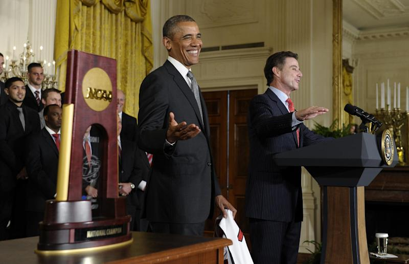 With the championship trophy sitting at left, President Barack Obama laughs as Louisville men's basketball coach Rick Pitino, right, says he was disappointed that he didn't meet first lady Michelle Obama during an event to honor the 2013 NCAA Men's Basketball Champions Louisville Cardinals, Tuesday, July 23, 2013, in the East Room of the White House in Washington. (AP Photo/Susan Walsh)