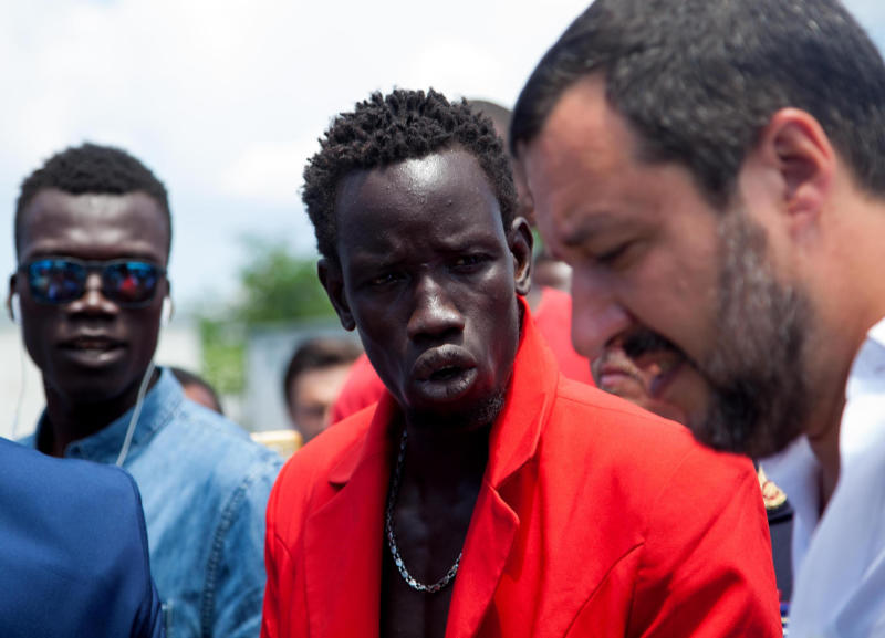 "Italian interior minister Matteo Salvini, right, listens to migrants during a visit to the San Ferdinando slum, near Reggio Calabria, Southern Italy, Tuesday, July 10, 2018. Italy's hard-line, anti-migrant interior minister has toured a crime-laden migrant shanty in southern Calabria and vowed to enforce only ""limited, controlled and qualified"" immigration. Matteo Salvini challenged the ""do-gooders"" who want to open Italy's ports to migrants to visit the San Ferdinando slum in Reggio Calabria, where he heard of shameless farmers exploiting migrant workers and women being forced into prostitution to get by. Last month, a migrant was killed in San Ferdinando by his former boss. (Marco Costantino/ANSA via AP)"