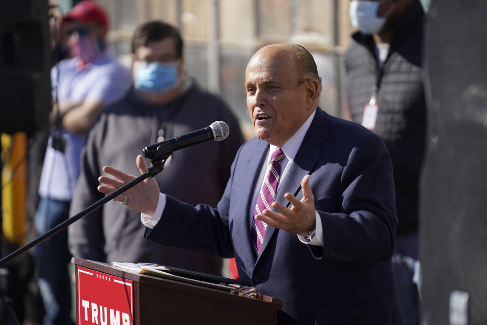 Mr Giuliani discovered that Joe Biden was announced as president-elect during the press conference (John Minchillo / AP)