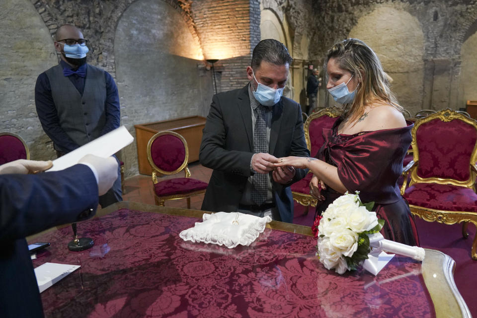 FILE - Tatiana Datolla, right, and Armando De Rosa exchange rings during their wedding ceremony, in Rome, at the deconsecrated Santa Maria in Tempulo church, Saturday, April 11, 2020. Under Italy's more relaxed lockdown rules starting next week, people can visit family within the same region. But confusion abounds over how close the family connection needs to be. Does a second cousin qualify? A third? A sister-in-law's kids? When asked to clarify Prime Minister Conte muddied the water even more, saying those with relations of 'stable affection' would qualify. That left Italians wondering whether girlfriends or boyfriends would pass the test. (AP Photo/Andrew Medichini)