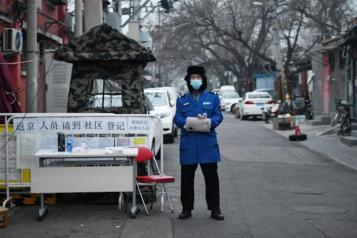 A security guard at the entrance to an alley in Beijing on Feb. 20. (Greg Baker/AFP via Getty Images)