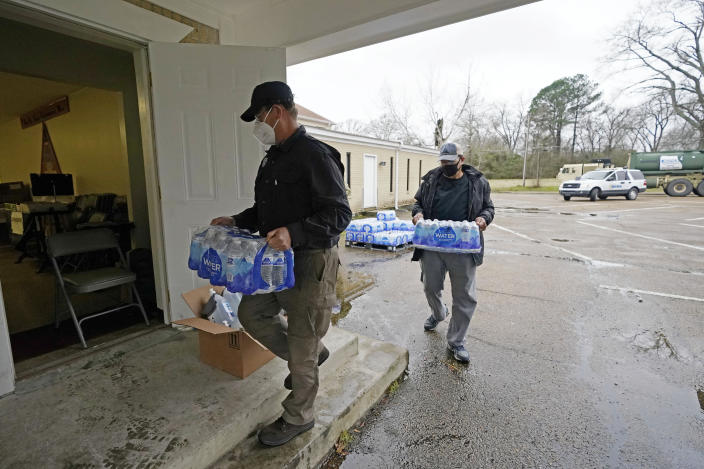 David Battaly with the Mississippi Emergency Management Agency, left, and Ralph Woullard, a member of the New Mt. Zion Missionary Baptist Church, carry cases of bottled water inside the church, Monday, March 1, 2021, at a Jackson, Miss., water distribution site on the church's parking lot. The bottled water as well as non-potable water was provided for area residents and was being distributed at seven sites in Mississippi's capital city — more than 10 days after winter storms wreaked havoc on the city's water system because the system is still struggling to maintain consistent water pressure, authorities said. (AP Photo/Rogelio V. Solis)