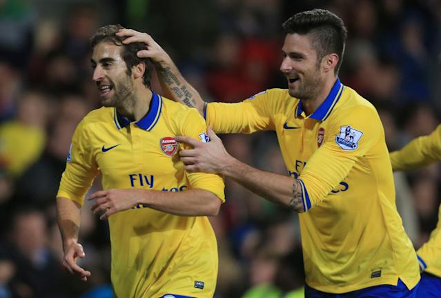Arsenal's Mathieu Flamini, left, celebrates scoring this team's second goal with teammate Olivier Giroud during their English Premier League soccer match against Cardiff City in Cardiff, Wales, Saturday, Nov. 30, 2013. (AP Photo/Nick Potts, PA Wire)