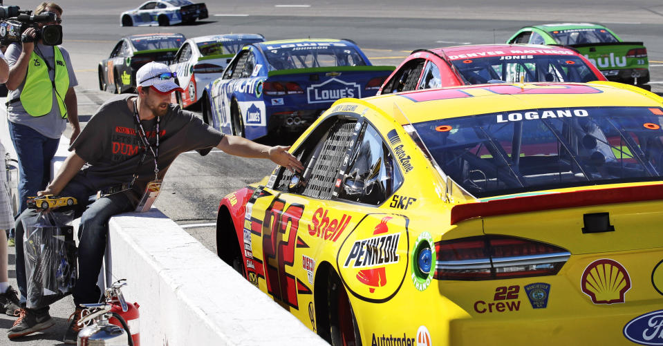 Joey Logano (22) sits parked in car as race fan Jason Wallace, of Ossipee, N.H., reaches over the wall to shake his hand during an afternoon practice for the NASCAR Cup Series 300 auto race at New Hampshire Motor Speedway in Loudon, N.H., Saturday, Sept. 23, 2017. Logano was penalized by officials for inspections violations and forced to sit parked on pit row for the entire practice. (AP Photo/Charles Krupa)