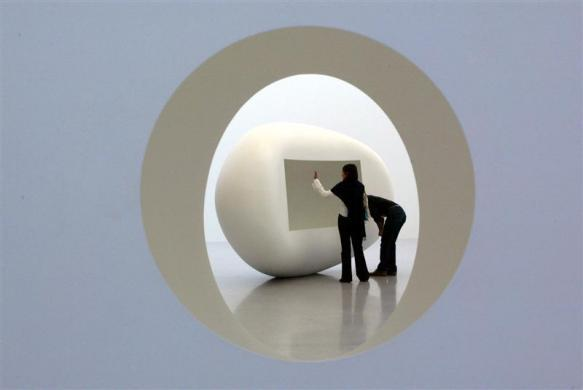 Visitors stands in front of a sculpture of artist Anish Kapoor in the Kunsthaus in Bregenz, Austria September 26, 2003.