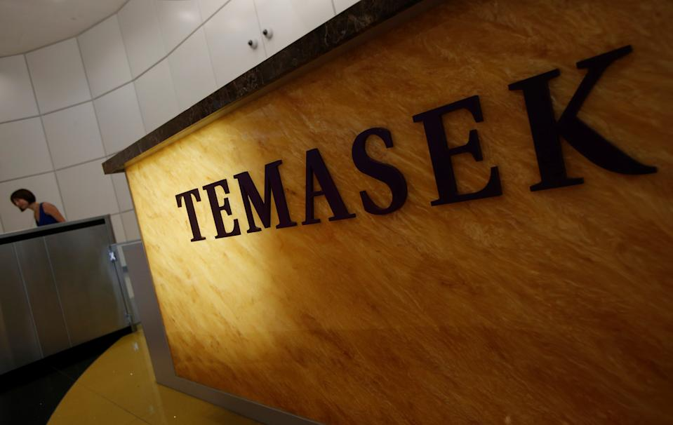 A woman passes a logo of state investor Temasek Holdings at their office in Singapore July 8, 2014. REUTERS/Edgar Su/File Photo
