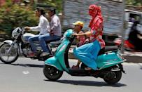A woman shields her face from the sun as she rides her scooter in Ahmedabad, India May 20, 2016. REUTERS/Amit Dave