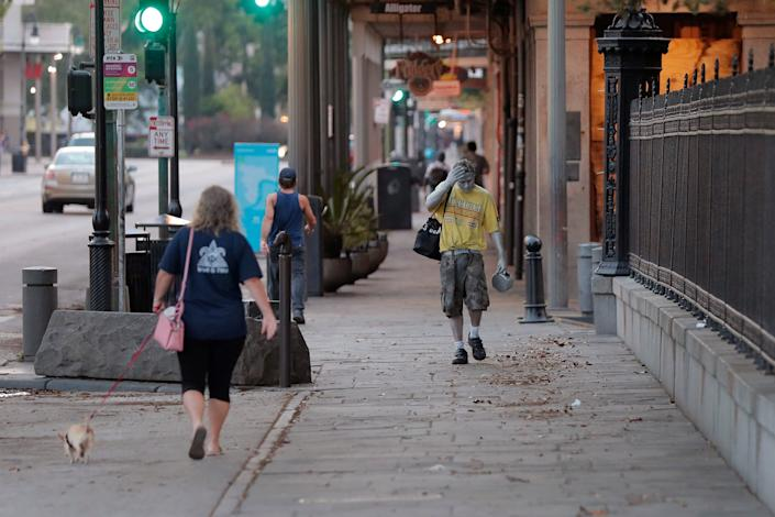 Street performer Eddie Webb walks through the nearly deserted French Quarter looking to make money in New Orleans, Sunday, March 22, 2020.