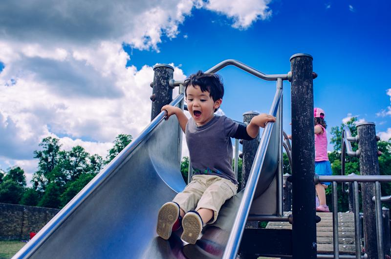 A young boy having fun sliding down a slide on a sunny day at a playground in Bushy Park London.