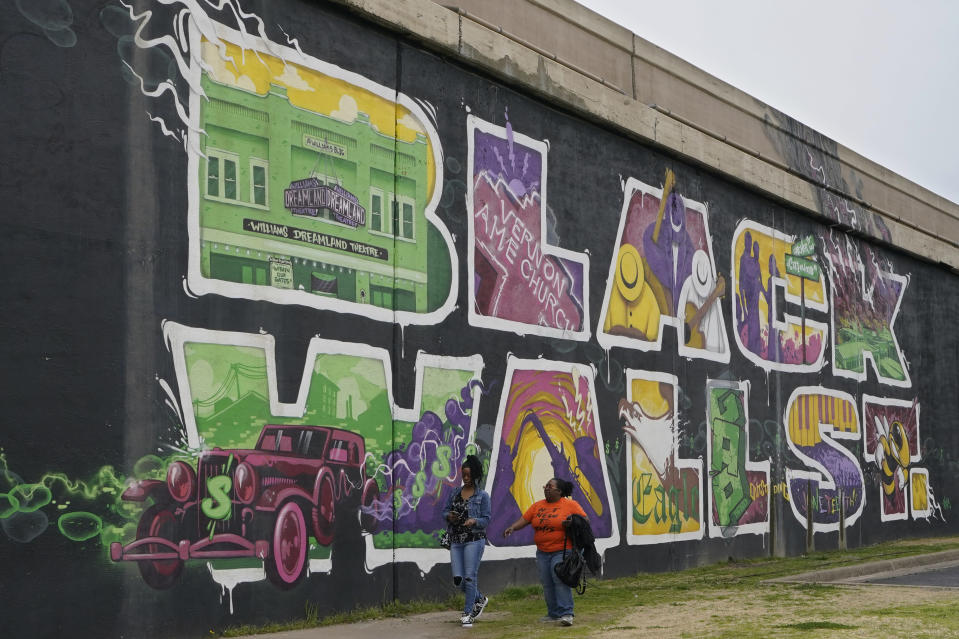 Javohn Perry, left, of Seattle, and her cousin, Danielle Johnson, right, of Beggs, Okla., walk past the Black Wall Street mural Monday, April 12, 2021, in Tulsa, Okla. The original Black Wall Street vaporized a hundred years ago, when a murderous white mob laid waste to what was the nation's most prosperous Black-owned business district and residential neighborhood. (AP Photo/Sue Ogrocki)