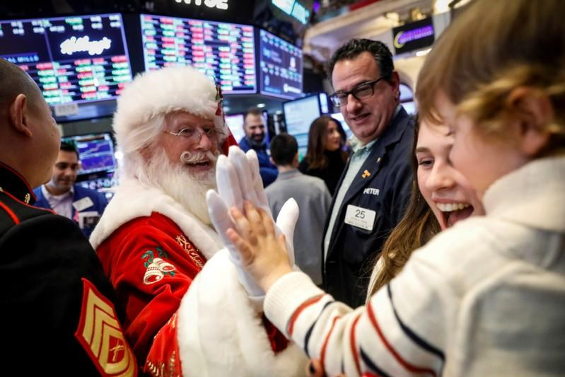 FILE PHOTO: Hudson Maloney, son to specialist trader Gregg Maloney, is given a high five by Santa Claus, on the floor during the traditional bring-your-kids-to-work day at the NYSE in New York