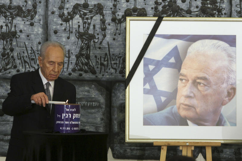 Israeli President Shimon Peres lights a candle for the late Israeli Prime Minister Yitzhak Rabin, as his picture stands nearby, during a memorial ceremony marking the 15th anniversary of his assassination, at the President's residence in Jerusalem, Tuesday, Oct. 19, 2010. Israel on Tuesday started marking the 15th anniversary of Rabin's assassination, according to the Jewish calendar. The late Israeli Prime Minister was killed by a Jewish extremist on November 4, 1995, after attending a peace rally. (AP Photo/Tara Todras-Whitehill)