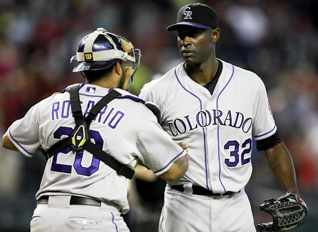 Colorado Rockies catcher Wilin Rosario (20) and relief pitcher LaTroy Hawkins (32) celebrate after defeating the Arizona Diamondbacks 5-3 in 10 innings in a baseball game, Sunday, Aug. 10, 2014, in Phoenix. (AP Photo/Rick Scuteri)