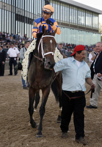 Overanalyze, with Rafael Bejarano aboard, is led to the winner's circle after winning the $1 million Arkansas Derby horse race at Oaklawn Park in Hot Springs, Ark., Saturday, April 13, 2013. (AP Photo/Danny Johnston)