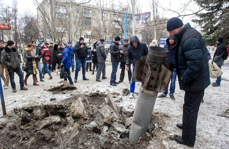 People look at a missile embedded in the street after shelling in eastern Ukrainian city of Kramotorsk on February 10, 2015 (AFP Photo/Volodymyr Shuvayev)