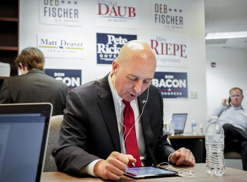Nebraska Gov. Pete Ricketts makes phone calls to voters, asking them to vote for him and for fellow Republican candidates, on primary election day, Tuesday, May 15, 2018, in Omaha, Neb. Gov. Ricketts is touting his conservative credentials on the national stage as he prepares for a showdown with the winner of Tuesday's Democratic gubernatorial primary. (AP Photo/Nati Harnik)