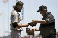 Pittsburgh Pirates pitcher JT Brubaker, left, is inspected by umpire Manny Gonzalez during the first inning of a baseball game against the San Francisco Giants in San Francisco, Sunday, July 25, 2021. (AP Photo/Jeff Chiu)