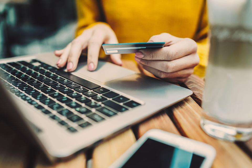 Woman's hands holding credit card and typing on keyboard on laptop (Photo: filadendron via Getty Images)