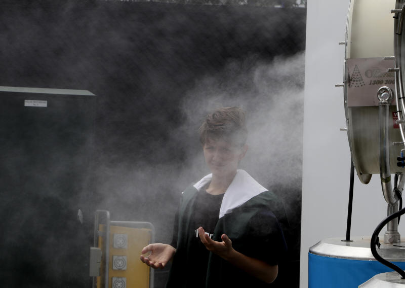 A spectator cools down in a front of a fan spraying water as qualifying matches continue ahead of the Australian Open tennis championship in Melbourne, Australia, Friday, Jan. 17, 2020. The season's opening Grand Slam event begins here Monday Jan. 20. (AP Photo/Mark Baker)
