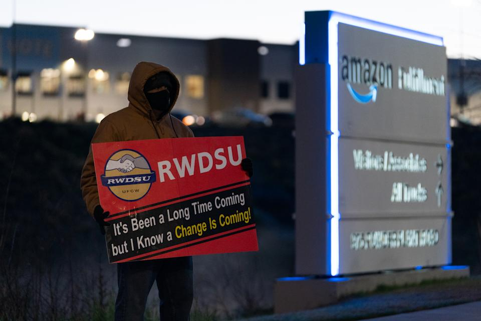BESSEMER, AL - MARCH 29: An RWDSU union rep holds a sign outside the Amazon fulfillment warehouse at the center of a unionization drive on March 29, 2021 in Bessemer, Alabama. Employees at the fulfillment center are currently voting on whether to form a union, a decision that could have national repercussions. (Photo by Elijah Nouvelage/Getty Images)