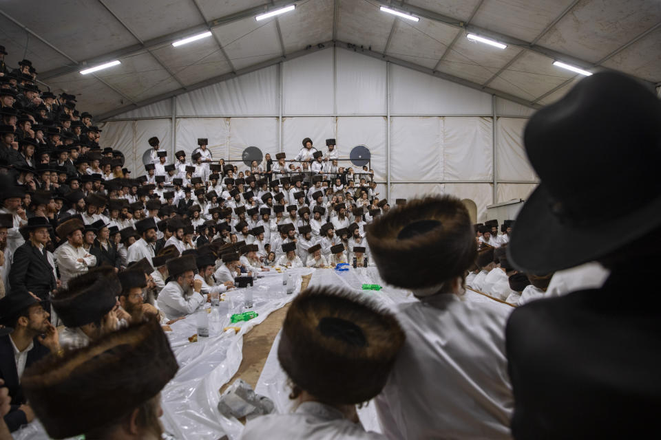 """Ultra-Orthodox Jews, members of the Lelov Hassidic dynasty attend the """"Pidyon Haben"""" ceremony for the great grandchild of their chief rabbi Aharon Biderman in Beit Shemesh, Israel, Thursday, Sept. 16, 2021. The Pidyon Haben, or redemption of the firstborn son, is a Jewish ceremony hearkening back to the biblical exodus from Egypt. (AP Photo/Oded Balilty)"""
