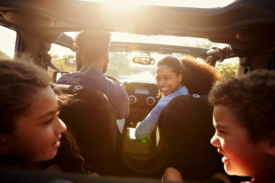 black mother and father and two young kids in car