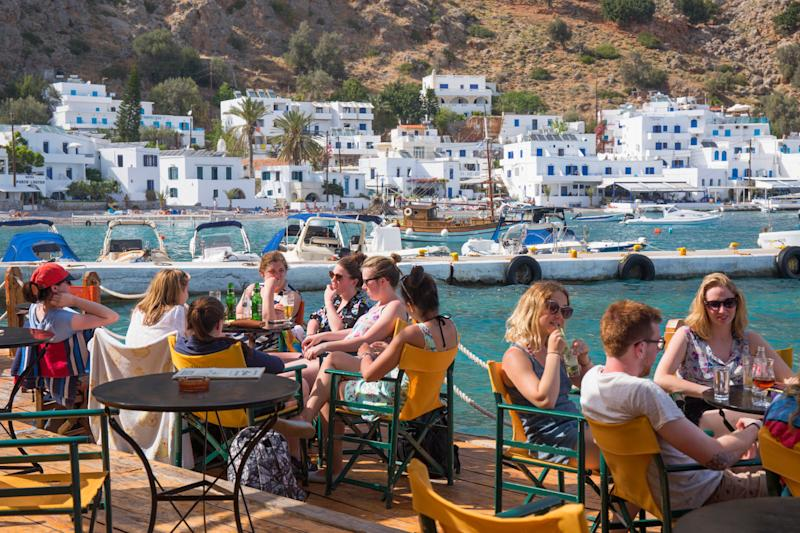 People relaxing on waterfront cafe terrace beside the harbour, Loutro,Hania, Crete | David C. Tomlinson—Getty Images/Lonely Planet Images