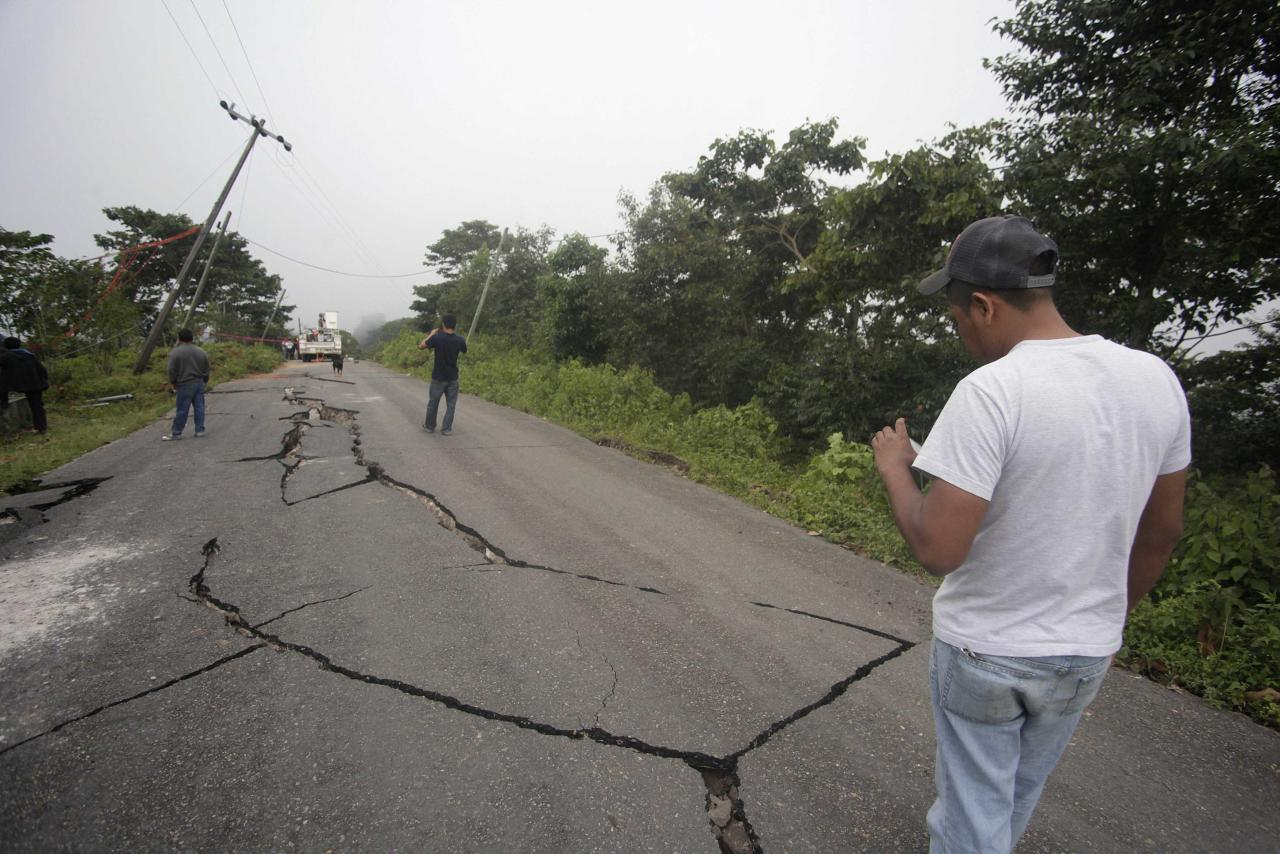 Residents take pictures of cracks in the road after an earthquake in the town of Union Juarez, in the Mexican state of Chiapas July 7, 2014. A strong earthquake shook the border between Guatemala and Mexico on Monday, killing at least three people, including a newborn boy, damaging dozens of buildings and triggering landslides. Much of the damage from the 6.9-magnitude quake was reported in the Guatemalan border region of San Marcos, where it downed power lines, cracked buildings and triggered landslides that blocked roads. REUTERS/Mario Castillo (MEXICO - Tags: DISASTER ENVIRONMENT)